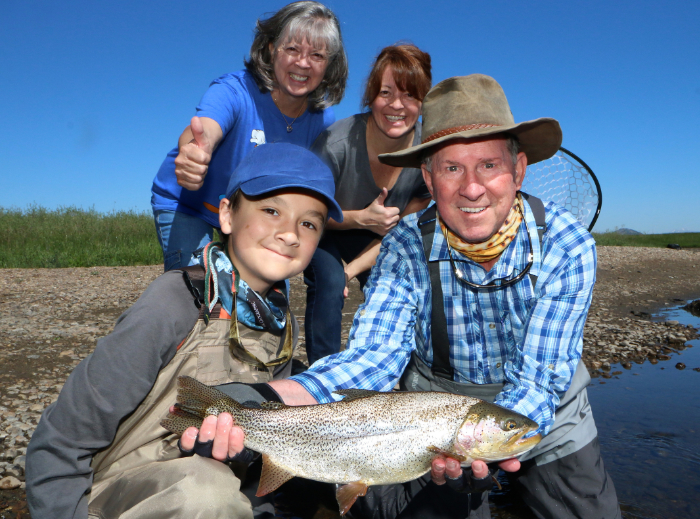 A happy family smiles for the camera and shows off their best catch of the day.