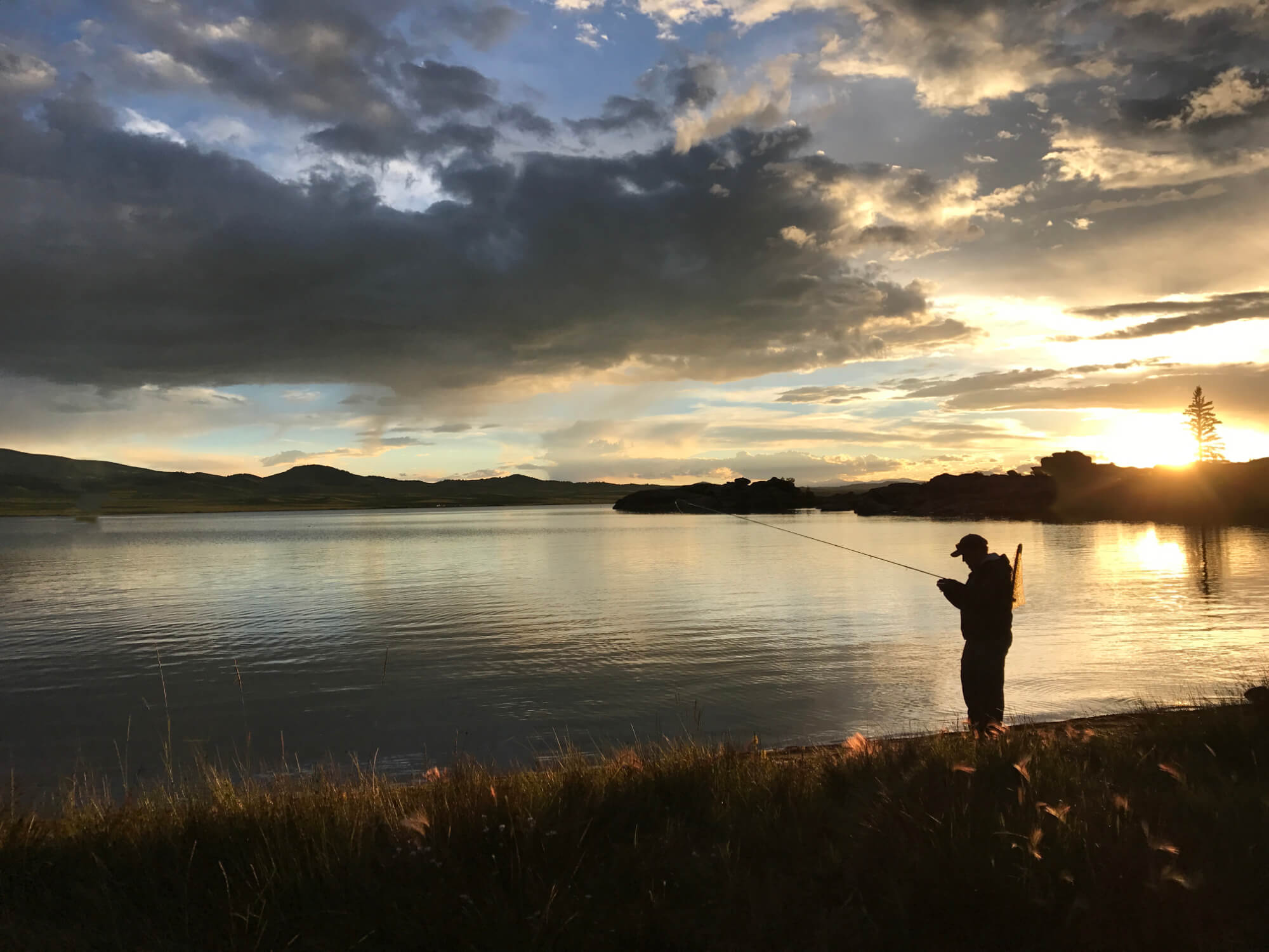 A fisherman stands on the banks of a Colorado reservoir at dawn.