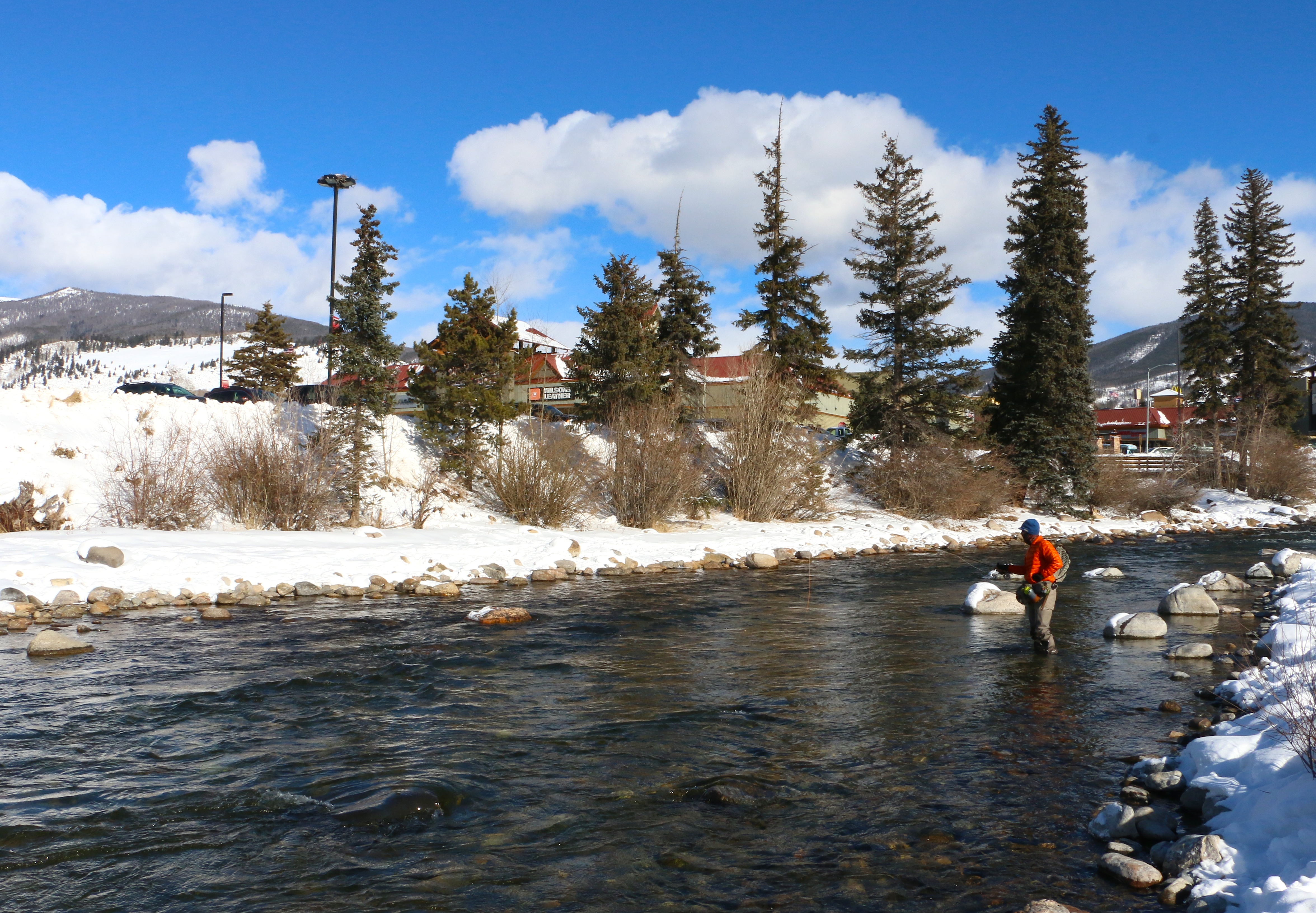 A fisherman casts his line in the blue river on a Colorado winter day.