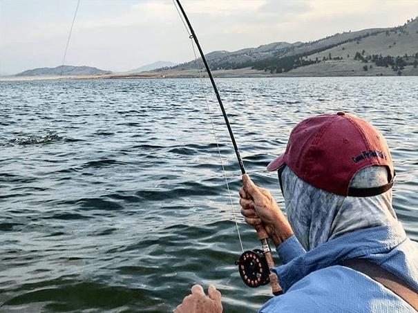 A fisherman casts his line into a Colorado lake.