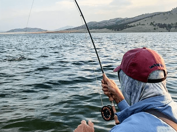 A fisherman casts his line into a Colorado lake.